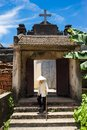 Hanoi, Vietnam - July 17, 2016: Aged church gate with Holy cross on top, Vietnamese old woman wear conical hat and stick walking i Royalty Free Stock Photo