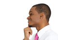 Happily daydreaming closeup side view profile portrait young man guy student employee worker thinking wondering chin on fist Stock Image