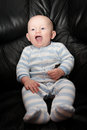 Happily lauging seated baby chubby boy with blue eyes laughing while sitting up Stock Images