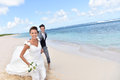 Happily married couple running on the sandy beach Royalty Free Stock Photo