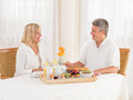 Happily mature senior married couple enjoy a healthy breakfast holding hands enjoying sitting at the table smiling at each other Royalty Free Stock Photos