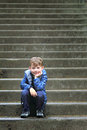 Happily waiting a cute little boy sitting on some big concrete steps smiling shallow depth of field copy space Stock Images