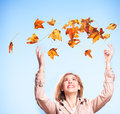 Happiness in autumn an attractive blonde woman throws sunlit leaves into the air with joy Stock Images