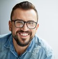 Happiness happy man in denim shirt and eyeglasses looking at camera with toothy smile Royalty Free Stock Photo