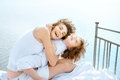 Happiness happy young mother and her kid embrace on vintage bed against sea Royalty Free Stock Photos