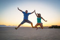 Happiness jump at sunset of the couple on desert Royalty Free Stock Image