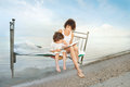 Happiness mother and kid read book vintage bed in water on sea shore Stock Photography