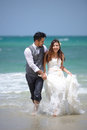Happiness and romantic scene of love just married couple walking young at beautiful beach Stock Photos