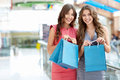 Happiness young girls with bags in a store Royalty Free Stock Photo