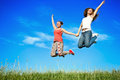 Happiness young women jumping two over blue sky Stock Photos