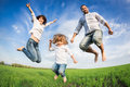 Happy active family jumping in green field against blue sky summer vacation concept Stock Photos