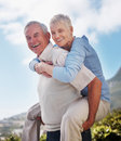Happy active older man giving woman piggyback ride Royalty Free Stock Photos