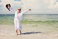 Happy active senior woman a smiling elderly on the beach with arms up Royalty Free Stock Images