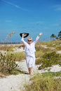 Happy active senior woman a smiling walking on the beach with arms up Royalty Free Stock Photos