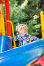 Happy adorable girl on children's slide on playground near kindergarten Montessori Royalty Free Stock Photo