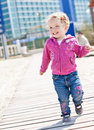 Happy adorable little girl running and laughing on the beach Stock Images