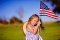 Happy adorable little girl smiling and waving american flag outs outside her dress with strip stars cowboy hat child Royalty Free Stock Photos