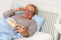 Happy adult woman with book lying on bed middle aged wearing eyeglasses holding a novel while her and looking at the camera Stock Photo