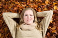 Happy adult woman enjoying the autumn season horizontal photo of a mature lying on a bed of leaves Stock Images