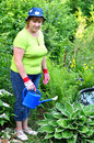 Happy adult woman gardener care for plants which grows near the pond in her garden Stock Image