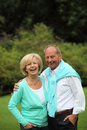 Happy affectionate senior couple standing arm in arm outdoors in a lush green park laughing at the camera Royalty Free Stock Photo