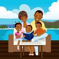 Happy african american family reading a book or looking a photo album sitting on outdoor sofa at the pool side Royalty Free Stock Photo