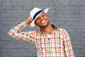 Happy african american guy with hat smiling in front of grey wall Royalty Free Stock Photo