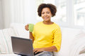 Happy african american woman with laptop at home Royalty Free Stock Photo