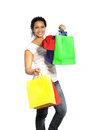 Happy african american woman shopper returning from a spending spree carrying handfuls of colourful shopping bags with her Royalty Free Stock Photos