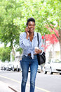 Happy african american woman walking on street with cell phone Royalty Free Stock Photo