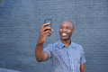 Happy african guy taking a selfie with his cell phone Royalty Free Stock Photo