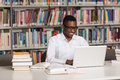 Happy African Male Student With Laptop In Library Royalty Free Stock Photo