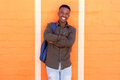 Happy african male student standing against orange wall with bag Royalty Free Stock Photo