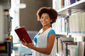 Happy african student girl reading book at library Royalty Free Stock Photo