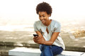 Happy african woman reading a text message on cellphone portrait of young sitting outside bench her mobile phone Stock Image