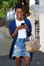 Happy african woman using mobile phone on the street Royalty Free Stock Photo