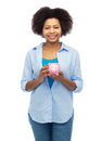 Happy afro american young woman with piggy bank