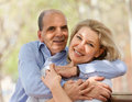 Happy aged lovers hugging each other and laughing in summer park Royalty Free Stock Photography