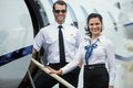 Happy airhostess and pilot standing on private portrait of confident jet s ladder Royalty Free Stock Photo