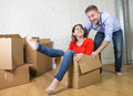 Happy American couple unpacking moving in new house playing with unpacked cardboard boxes