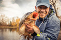 Happy angler with carp fishing trophy Royalty Free Stock Photos