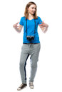 Happy animated young woman with a camera slung around her neck gesturing her hands and looking off to the right of the frame Royalty Free Stock Photography