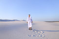 Happy Arab man walks in middle of white desert and enjoys life o