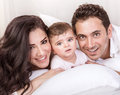 Happy arabic family closeup portrait of beautiful mother and handsome father with baby daughter lying down and having fun in Stock Image