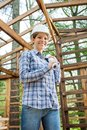 Happy architect holding blueprint in wooden cabin portrait of female incomplete at construction site Royalty Free Stock Photo