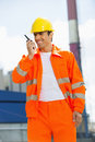 Happy architect wearing reflective workwear communicating on walkie talkie at site Stock Photo