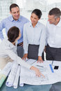 Happy architects interacting and analyzing plans together in bright office Royalty Free Stock Photos