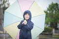 Happy asian boy holding colorful umbrella playing in the park Royalty Free Stock Photo