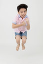 Happy asian boy is jumping at studio. Royalty Free Stock Photo