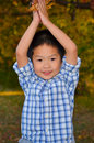 Happy Asian Boy Playing With Autumn Leaves Royalty Free Stock Photography